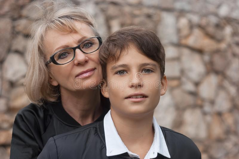 Good-looking, single-parent mom and teen son in the park. Photo. Close up and copy space. Cohesion, friendship and family relations royalty free stock photos