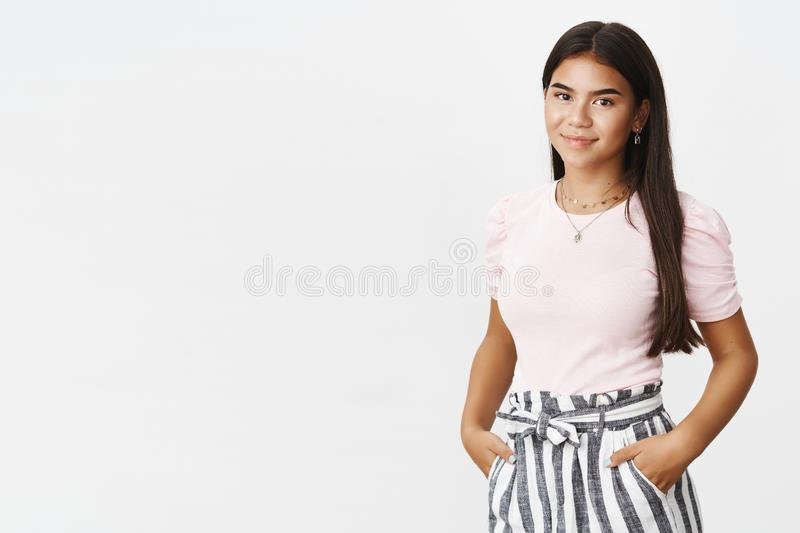 Good-looking stylish and hapyp nice charming indian teenager in pants and t-shirt holding hands in pockets smiling. Friendly at camera as posing carefree and royalty free stock image