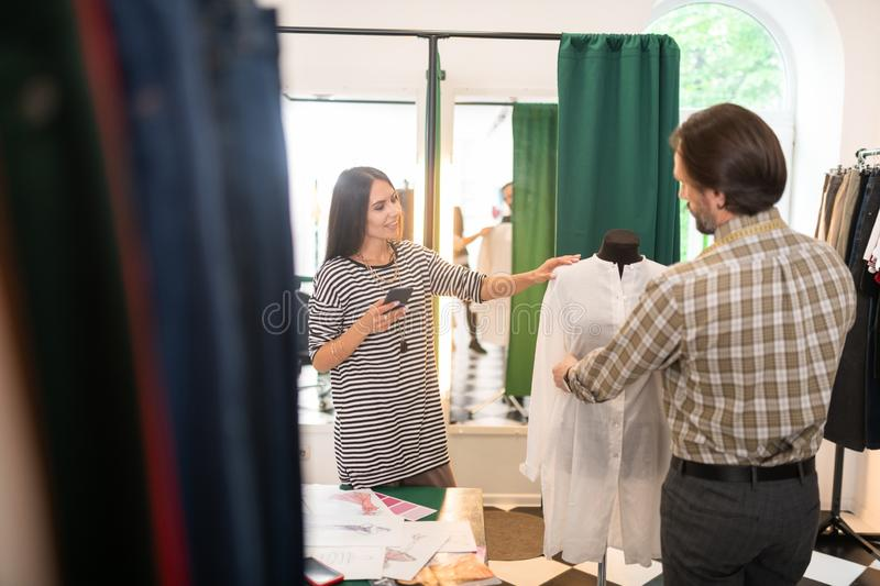 Good-looking talented fashion designer getting measurements of a dress stock image