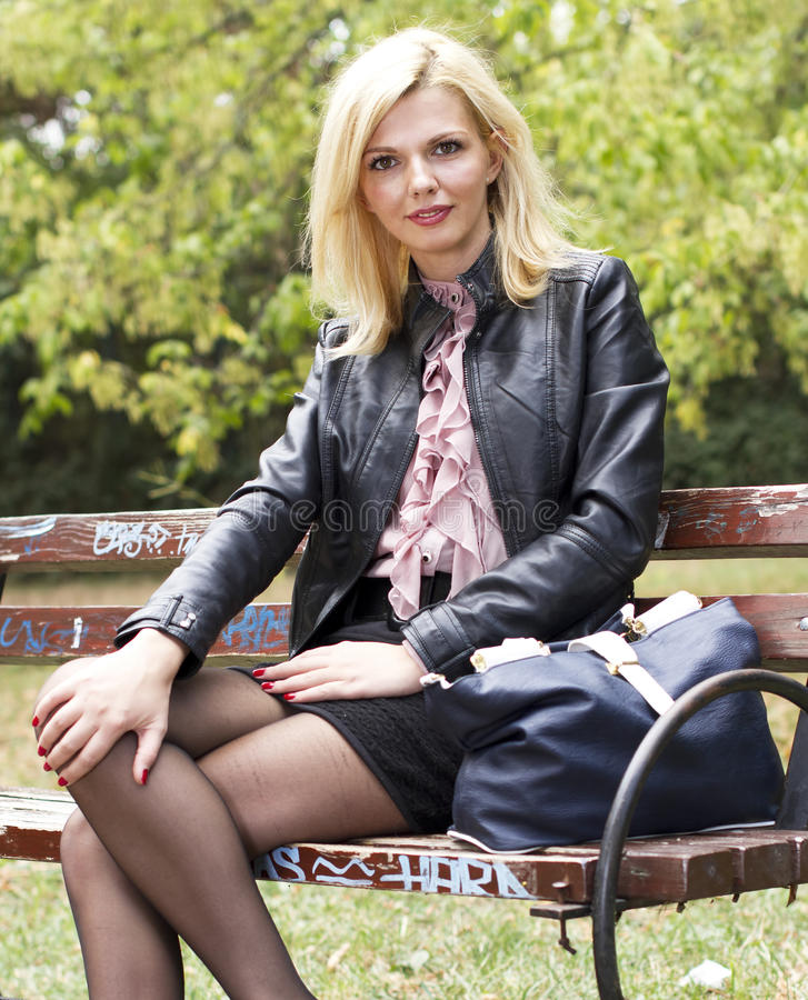 Good looking woman standing on a bench stock photography