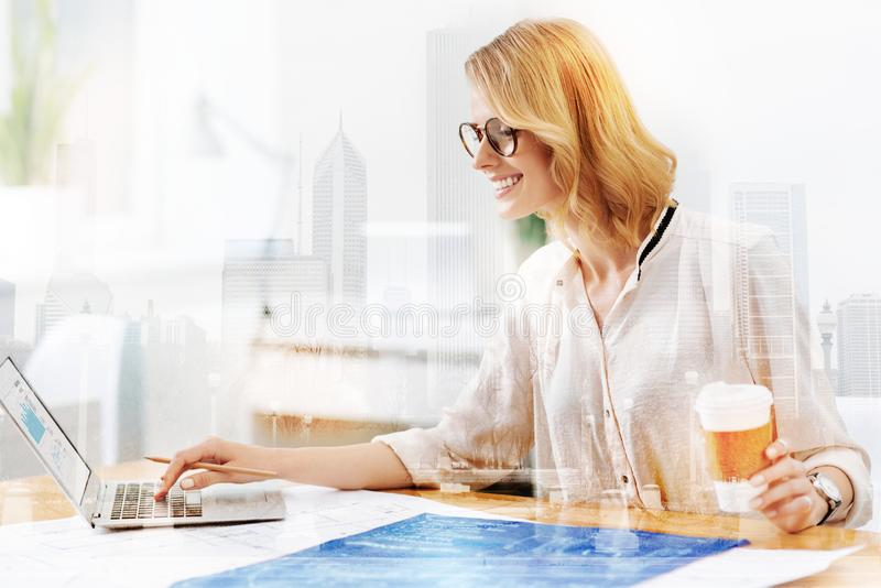 Good looking woman working with a laptop and sketches stock photography