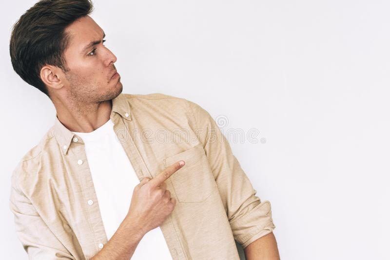 Good-looking young Caucasian man dressed in white t-shirt and beige shirt, pointing aside with hand and finger to the blank copy stock images