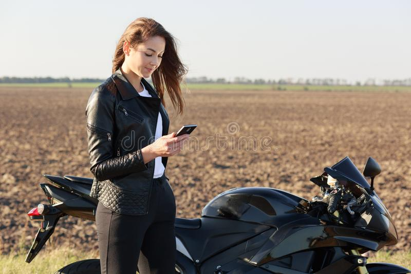 Good looking young female biker wears red stylish bandana and black clothes, holding mobile phone in hands, types text message,. Uses modern electronic device stock image