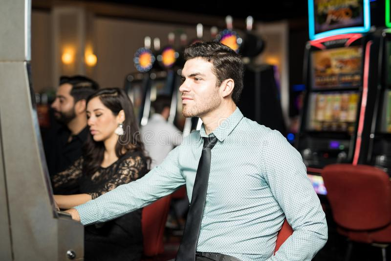Young man playing in slot machines royalty free stock photography