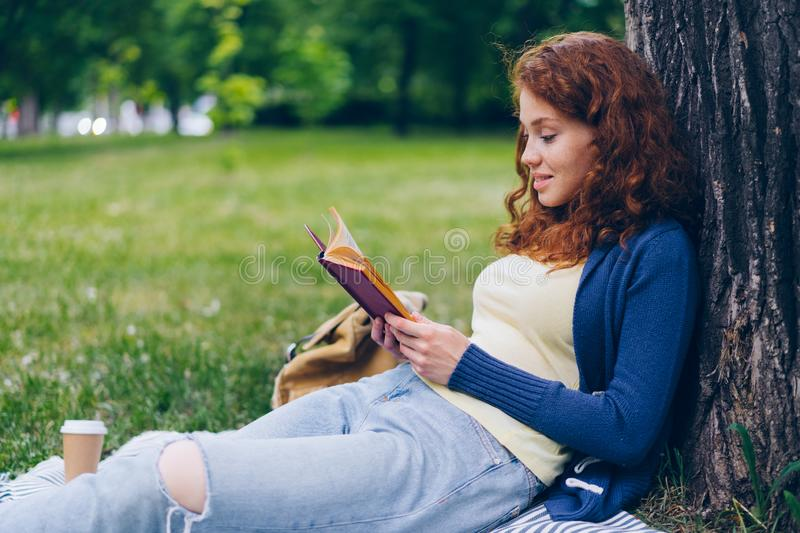 Good-looking young lady reading book and smiling sitting on lawn in park stock photography