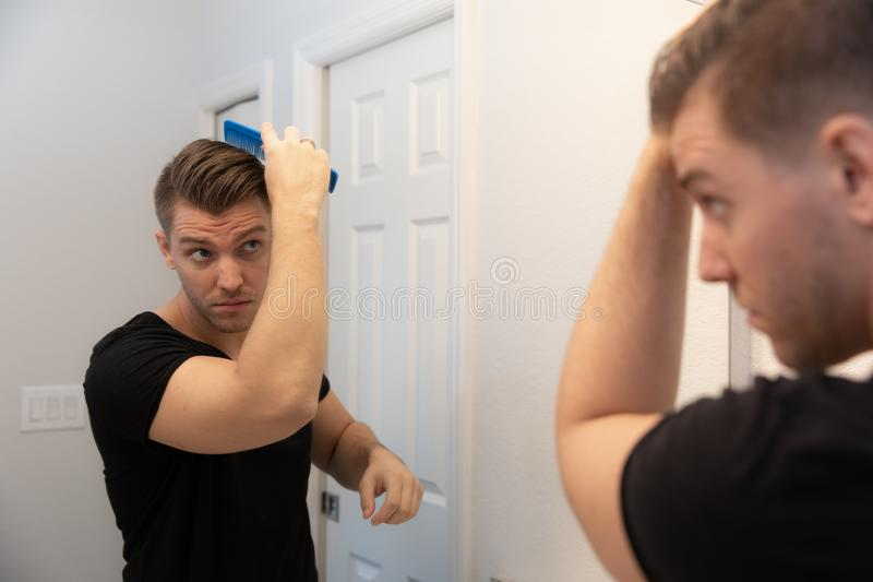 Good Looking Young Man Combing and Looking at His Hair, Beard, and Face in His Home Bathroom Mirror in the Morning Getting Ready f. Or a Good Day in the world royalty free stock photo