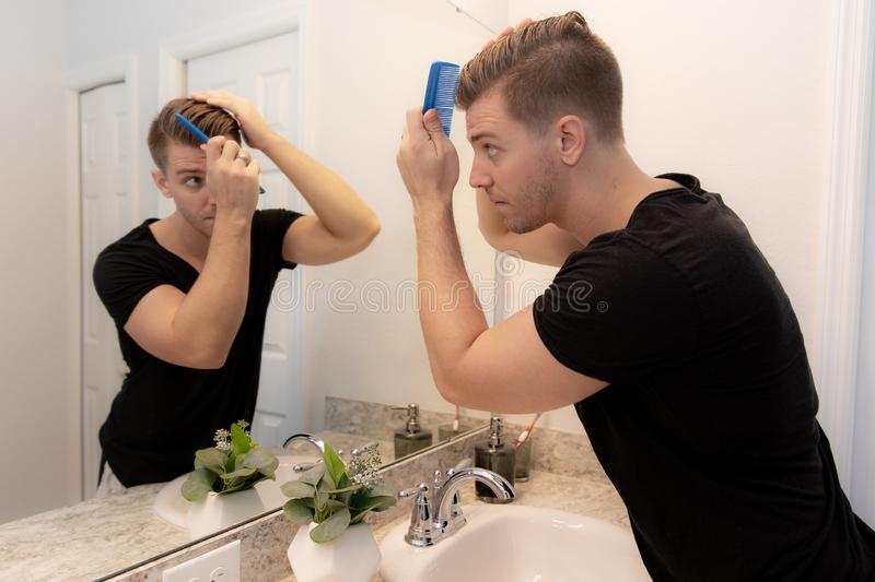 Good Looking Young Man Combing and Looking at His Hair, Beard, and Face in His Home Bathroom Mirror in the Morning Getting Ready f. Or a Good Day in the world stock photos