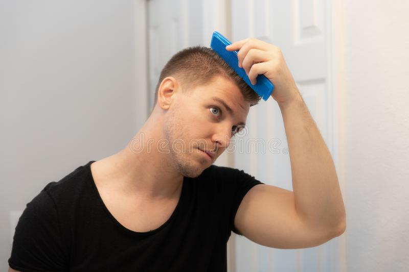 Good Looking Young Man Combing and Looking at His Hair, Beard, and Face in His Home Bathroom Mirror in the Morning Getting Ready f. Or a Good Day in the world royalty free stock photography