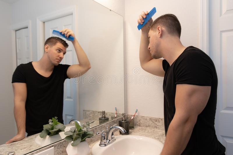 Good Looking Young Man Combing and Looking at His Hair, Beard, and Face in His Home Bathroom Mirror in the Morning Getting Ready f. Or a Good Day in the world royalty free stock image