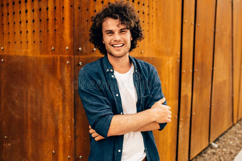 Good-looking young man with curly hair, smiling and standing at modern metal building wall outdoors. Portrait of happy smart stock photos