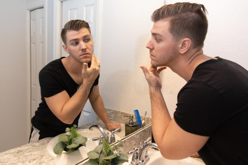 Good Looking Young Man Looking and Examining His Beard and Face in His Home Bathroom Mirror in the Morning Getting Ready for a Goo. Good Looking Young Man with royalty free stock image