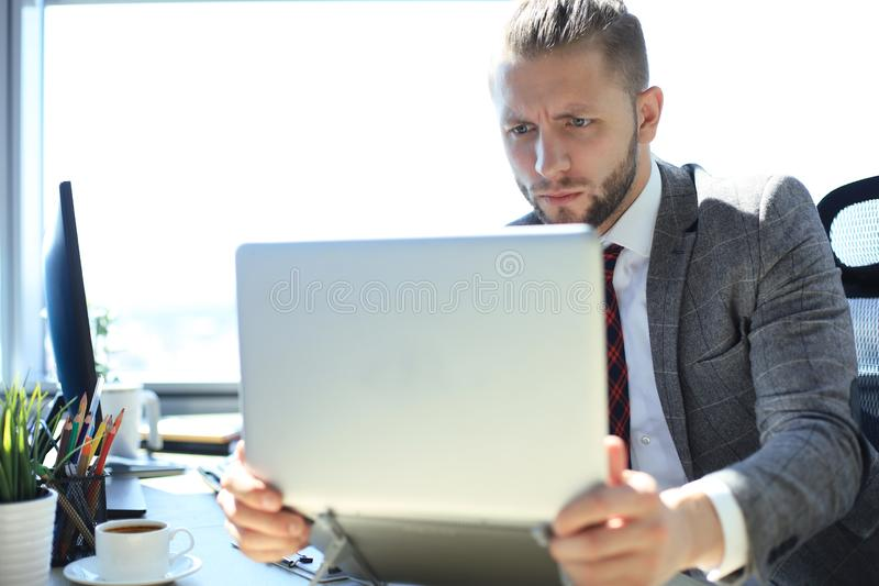 Good looking young man in full suit holding laptop while sitting in the office.  stock photos