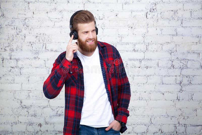 Good looking young man listening music and looking away while standing against white brick wall royalty free stock photography