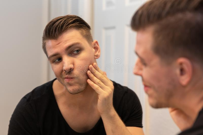 Good Looking Young Man Looking and Examining His Beard and Face in His Home Bathroom Mirror in the Morning Getting Ready for a Goo. Good Looking Young Man with stock images