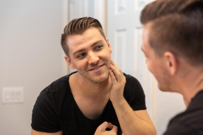 Good Looking Young Man Looking and Examining His Beard and Face in His Home Bathroom Mirror in the Morning Getting Ready for a Goo. Good Looking Young Man with stock image
