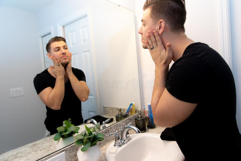 Good Looking Young Man Washing Hands and Face in Home Bathroom Mirror and Sink Getting Clean and Groomed During Morning Routine. After taking a shower and stock images