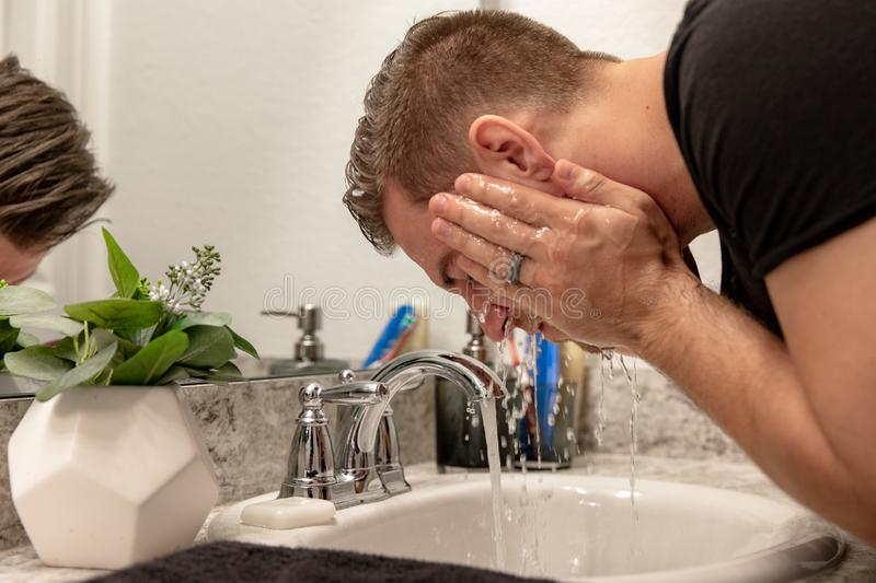 Good Looking Young Man Washing Hands and Face in Home Bathroom Mirror and Sink Getting Clean and Groomed During Morning Routine. After taking a shower and stock photo