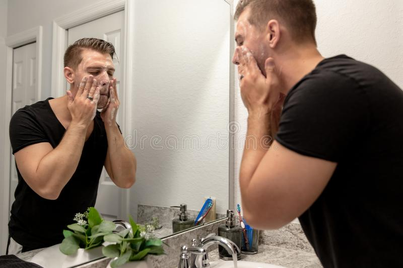 Good Looking Young Man Washing Hands and Face in Home Bathroom Mirror and Sink Getting Clean and Groomed During Morning Routine. After taking a shower and stock image