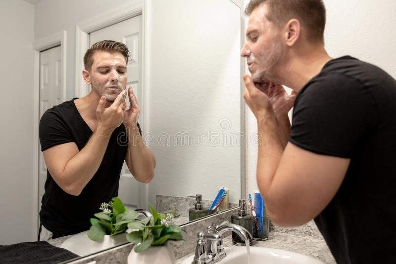 Good Looking Young Man Washing Hands and Face in Home Bathroom Mirror and Sink Getting Clean and Groomed During Morning Routine. After taking a shower and royalty free stock image