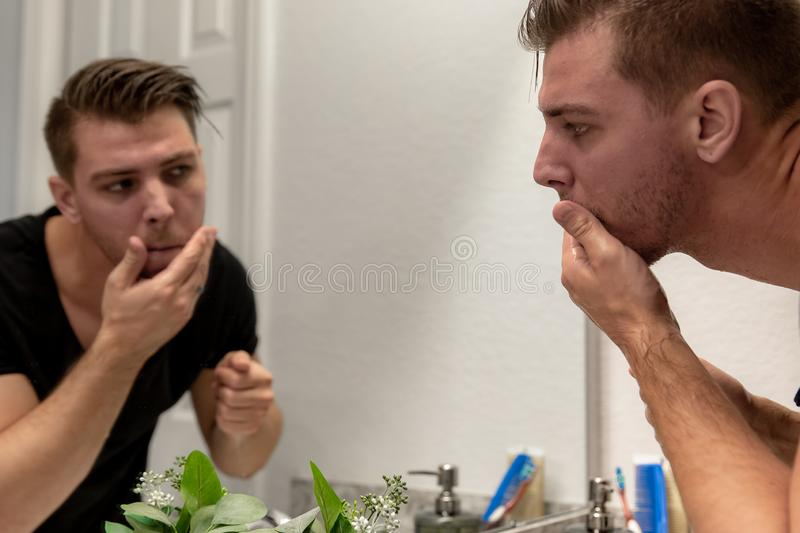 Good Looking Young Man Washing Hands and Face in Home Bathroom Mirror and Sink Getting Clean and Groomed During Morning Routine. After taking a shower and royalty free stock photography