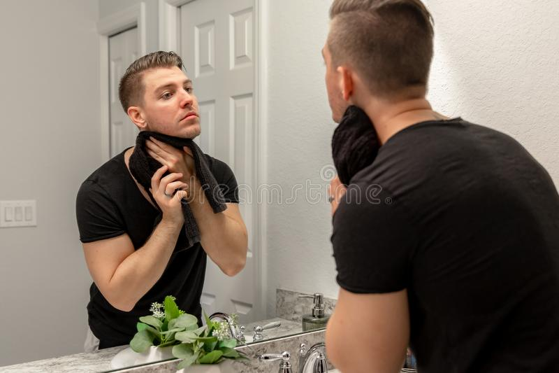 Good Looking Young Man Washing Hands and Face in Home Bathroom Mirror and Sink Getting Clean and Groomed During Morning Routine. After taking a shower and royalty free stock photos
