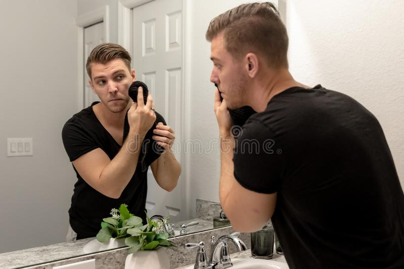 Good Looking Young Man Washing Hands and Face in Home Bathroom Mirror and Sink Getting Clean and Groomed During Morning Routine. After taking a shower and royalty free stock photo
