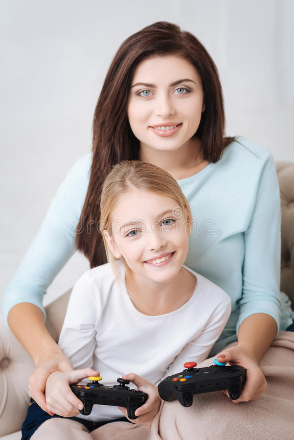 Good looking young mother playing with her daughter royalty free stock images