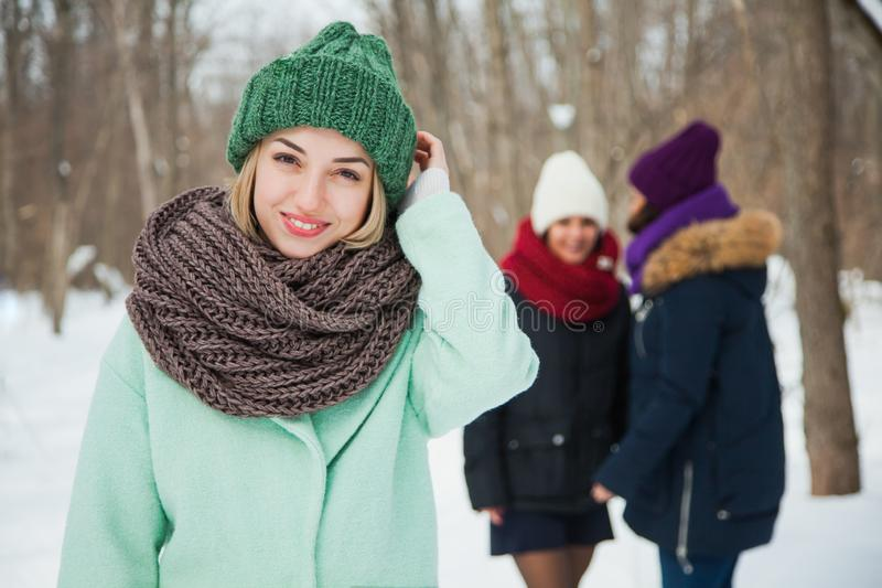 Good looking young woman in purple knitted hat and snood posing outdoors. Good looking young women in green knitted hat and snood posing outdoors. One happy stock photography