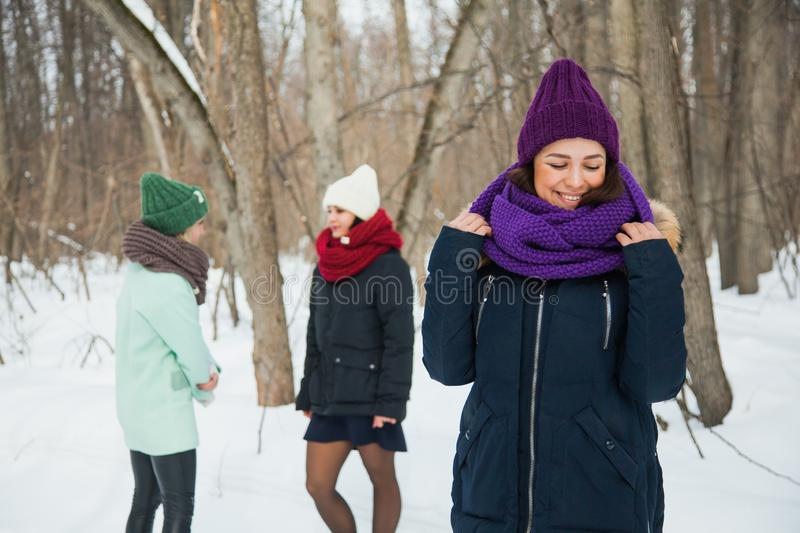Good looking young woman in purple knitted hat and snood posing outdoors. Good looking young women in purple knitted hat and snood posing outdoors. One happy royalty free stock photo