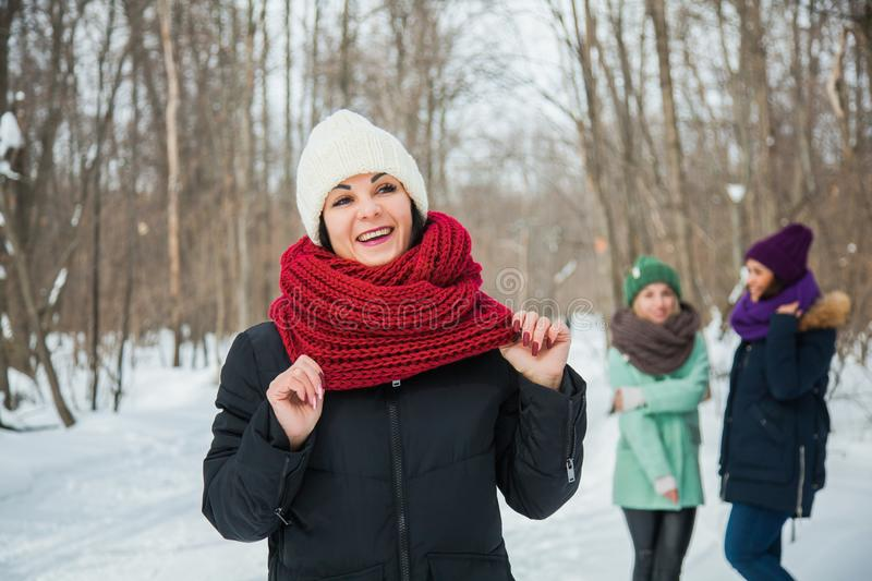 Good looking young woman in purple knitted hat and snood posing outdoors. Good looking young women in white knitted hat and snood posing outdoors. One happy stock image