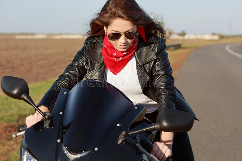 Good looking young woman in stylish black leather jacket, red bandana and sunglasses, rides motorbike, poses on road with no peopl. E and transport, enjoys high stock image