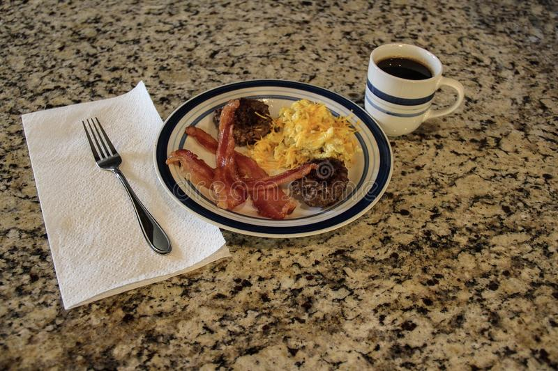 Good low carb breakfast. Delicious low carbohydrates breakfast with pork sausage bacon scrambled eggs shredded cheddar cheese and black coffee royalty free stock photo