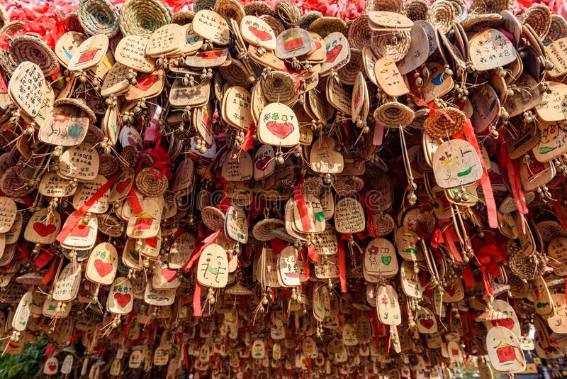 Good luck amulet charms, Yunan, China. Yunnan, China - 22 March 2016: Wooden good luck charms writen with various wishes. Lijiang ancient town royalty free stock image