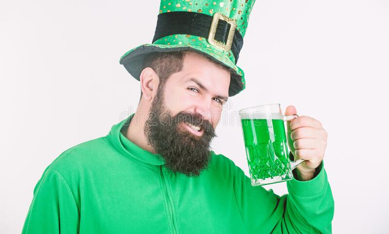 For good luck. Bearded man toasting to saint patricks day. Hipster in leprechaun hat holding beer mug. Irish man with stock photography