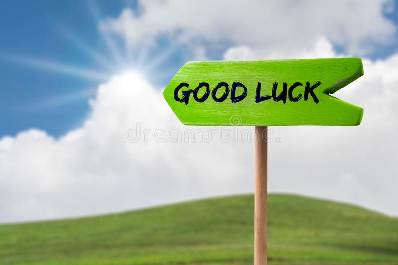 Good luck arrow sign. Good luck green wooden arrow sign on green land with clouds and sunshine stock image