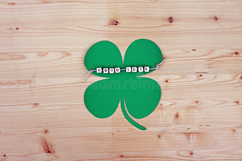 Good Luck. The words Good Luck and a cloverleaf on a cord on wood stock image