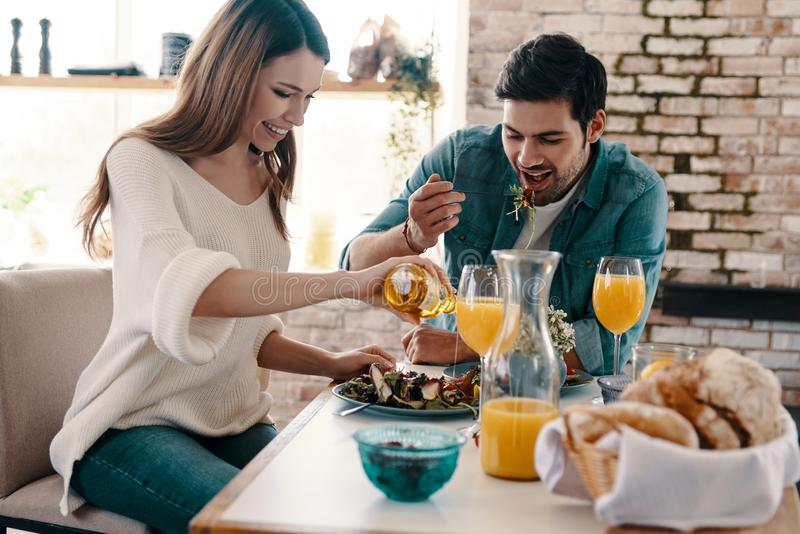 Good meal in a good company. Beautiful young couple enjoying healthy breakfast while sitting in the kitchen at home royalty free stock images