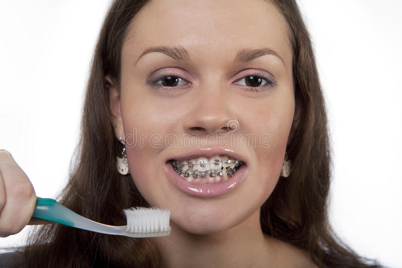 Good morning!. Nice young dark hair girl holding toothbrush and wearing bracket system isolated over white royalty free stock images