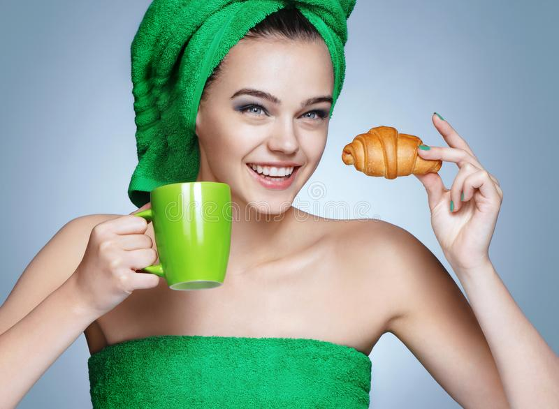 Good morning! Attractive girl in green towels with cup of coffee and croissant stock image