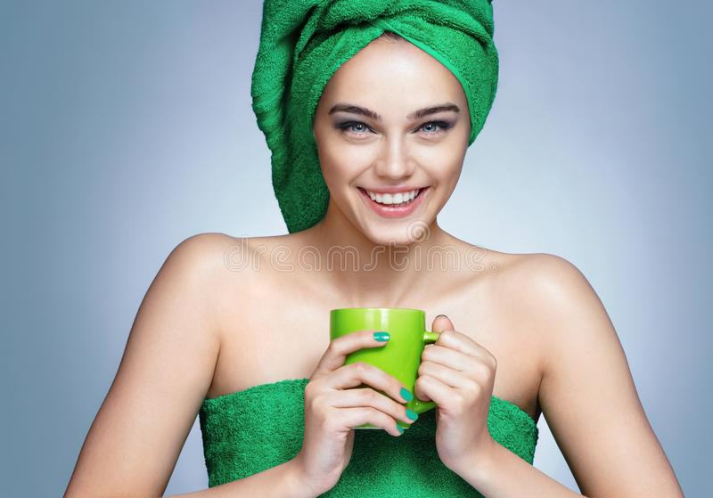 Attractive girl in green towels with cup of tea on blue background. royalty free stock images
