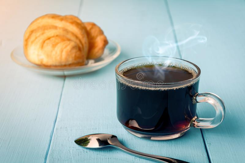 Good morning black coffee cup. And bread on a wooden table in the sunrise background. breakfast and wake up stock photography