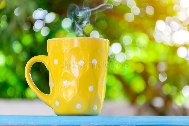 Good morning black coffee cup. And flower on a wooden table in the sunrise background. breakfast and wake up stock photo