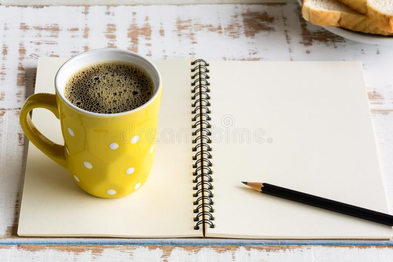 Good morning black coffee cup. And notebook on a wooden table in the sunrise background. breakfast and wake up stock photo
