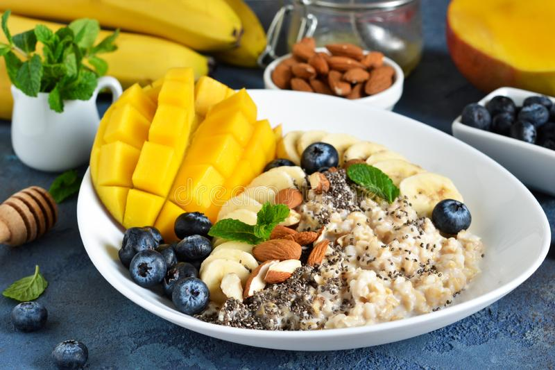 Good morning! Breakfast with oatmeal, banana, mango, blueberries and chia seeds on a concrete background stock photos