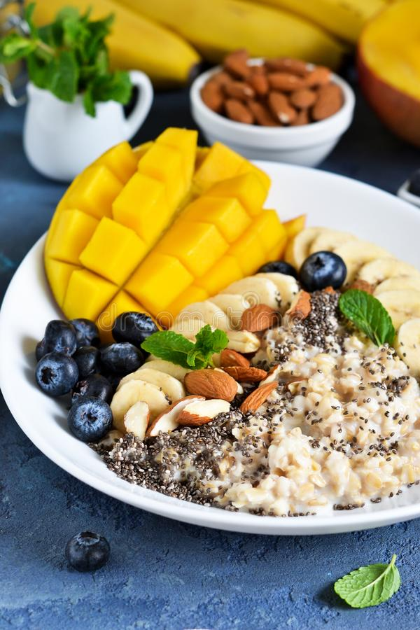Good morning! Breakfast with oatmeal, banana, mango, blueberries and chia seeds on a concrete background stock image