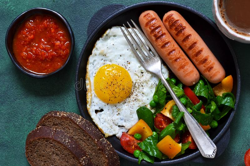 Good morning! Breakfast with sausage, egg, salad and tomato. Sauce with a cup of coffee on a green concrete background royalty free stock images