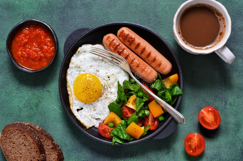 Good morning! Breakfast with sausage, egg, salad and tomato. Sauce with a cup of coffee on a green concrete background royalty free stock image