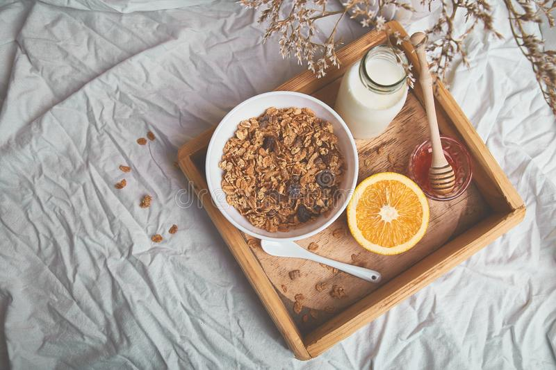 Good morning. Breakfast on white bed sheets. Muesli or granola, milk, orange on wooden tray from above. Top view. Flat lay. Copy space. Hotel Room Early stock photo