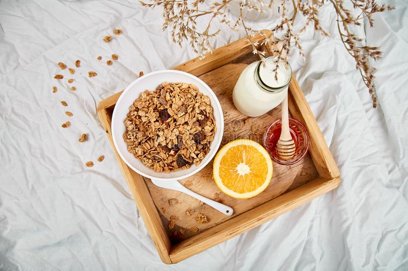 Good morning. Breakfast on white bed sheets. Muesli or granola, milk, orange on wooden tray from above. Top view. Flat lay. Copy space. Hotel Room Early royalty free stock photography