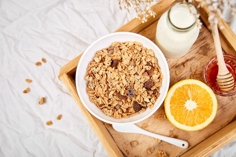 Good morning. Breakfast on white bed sheets. Muesli or granola, milk, orange on wooden tray from above. Top view. Flat lay. Copy space. Hotel Room Early stock images